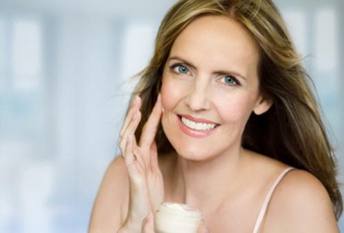 Женщина после 40 наносит на лицо крем