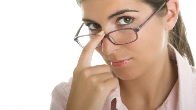 Девушка в очках прикасается пальцем к носу