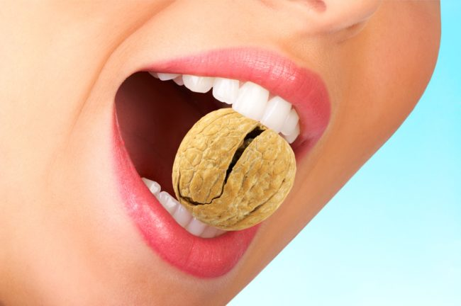 Девушка разгрызает орех
