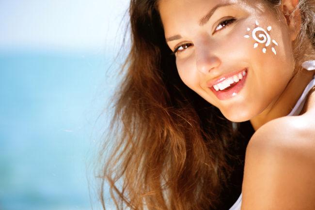 Девушка с солнцезащитным кремом на лице